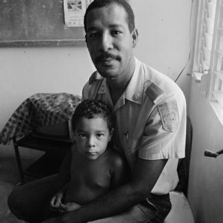 A gelatin silver print of a man and his child sitting in a room.