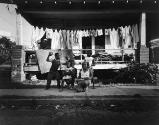 Hudnall's gelatin silver print of kids playing on the sidewalk in front of a house with drying laundry behind them.