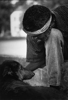 Hudnall's gelatin silver print of a man petting a dog.