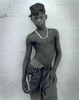 Hudnall's gelatin silver print of a young boy posing on a wall.