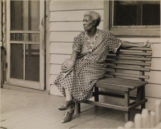 McNeill's gelatin silver print of a woman on a bench outside of a house.