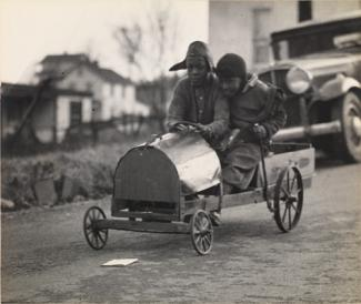 McNeill's gelatin silver print of two boys in a homemade racer.