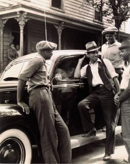 McNeill's gelatin silver print of four men around a car.