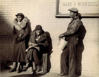 McNeill's gelatin silver print of three figures waiting against a wall.
