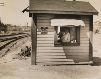 McNeill's gelatin silver print of a man in a small house by the railroad.