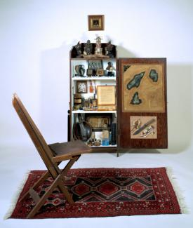 Stout's mixed media with a chair on a carpet and a shelf behind it.