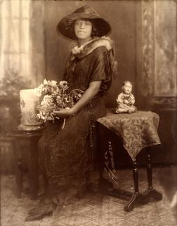 VanDerZee's gelatin silver print of a lady sitting on a table with flowers in her hands.