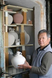 An image of Cliff Lee in his studio holding a porcelain bowl.
