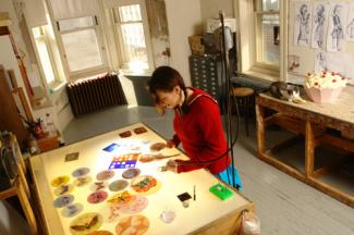 An image of artist Judith Schaechter in her studio producing work.