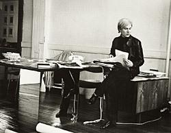 A picture of Andy Warhol sitting at a desk.