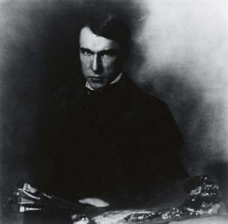 A black and white photograph of a man sitting down with paint brushes in his hand.