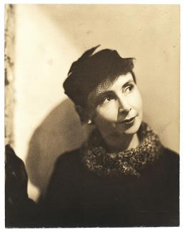 A photograph of a woman with a coat and a hat.