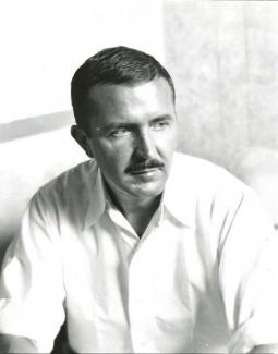 A black and white photograph of a man sitting down.