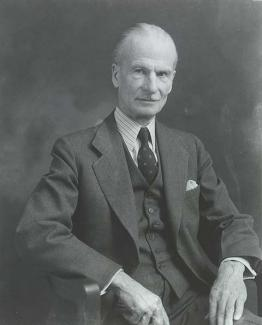 A photograph of a man sitting in a chair in a suit.