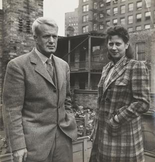 A photograph of a man and wife standing outside in coats.