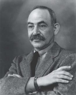 A photograph of a man sitting in a suit with his arms folded.