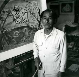 A image of a man in white holding a brush in front of a painting.