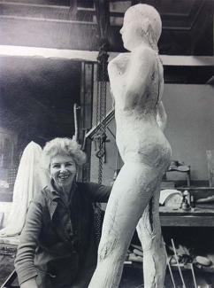 A photograph of a woman next to a sculpture of a human figure.