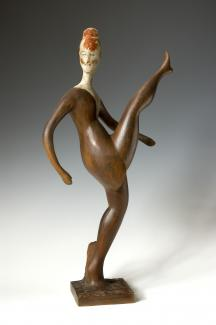 A sculpture made of wood of a dancer kicking their leg up in the air.