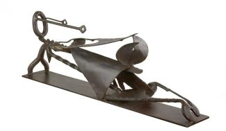 An iron sculpture of a figure reclining.