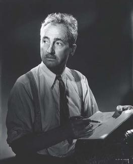 A photograph of a man sitting with pen and paper in hand.