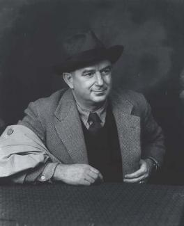 A photograph of a man sitting down with a jacket and hat.