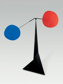 a black steel sculpture with two circles in red and blue.