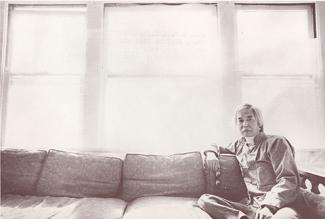 A photograph of a man sitting on a couch.