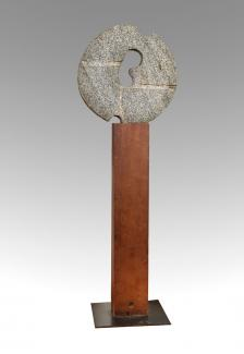 A granite circular sculpture on a wooden stand.