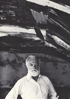 A photograph of a man standing in front of a painting.