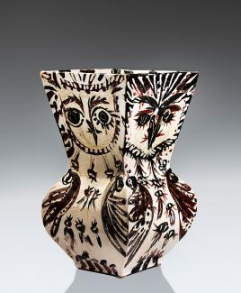 A ceramic vase painted with owl faces on each side.
