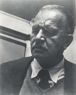 A photograph of a man in a tie with glasses on his forehead.