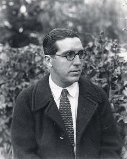 A photograph of a man in glasses with a coat and tie.
