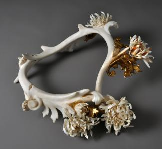 A neckpiece made of antler and bone painted gold.