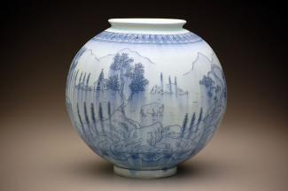 A photograph a porcelain circular pot with blue pencil like drawings.