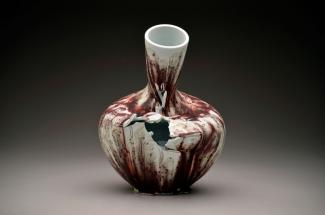 A photograph of a porcelain vase that has a hole in it and is leaning over.