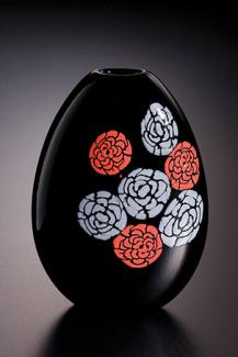 A black glass vessel with red and white flowers.