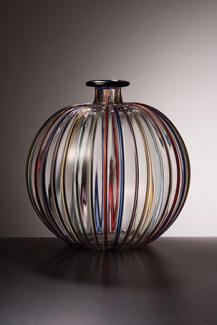 A clear glass vessel with rainbow colors painted in stripes down the side.
