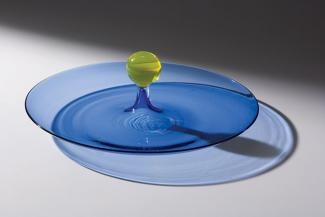A clear blue glass plate with a yellow glass ball in the middle.