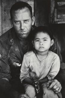 A photograph of a man holding a child in his lap.