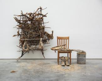 Sculpture formed from sticks, mud, and rope on a wall, with a chair and bucket positioned to the right of it