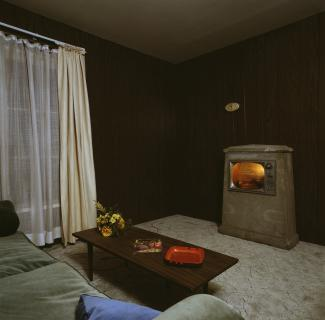 Interior of dark, wood-paneled living room with television facing a sofa