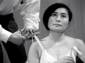 A photograph of a man cutting a womans bra strap.