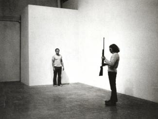 A photograph of two men, one with a gun pointing up and another against a wall.
