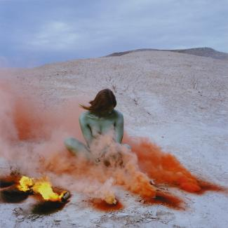 A photograph of a woman sitting down in nature with fire and red smoke around her.