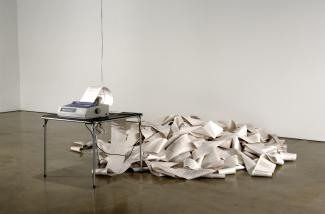 A photograph of a printer with paper overflowing onto the floor of a gallery.