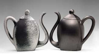 Two ceramic teapots in black.