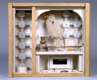 A box with a paper bird inside and many small clocks.