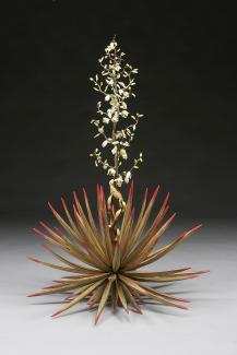 A ceramic plant with orange and red flowers at the bottom and a long stem with small white flowers.