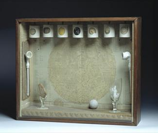 A box with seven things hanging from the top and a glass inside.